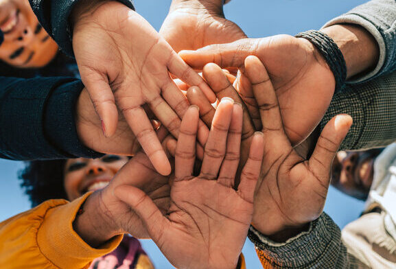 group of friends stacking hands and all connected to support one another