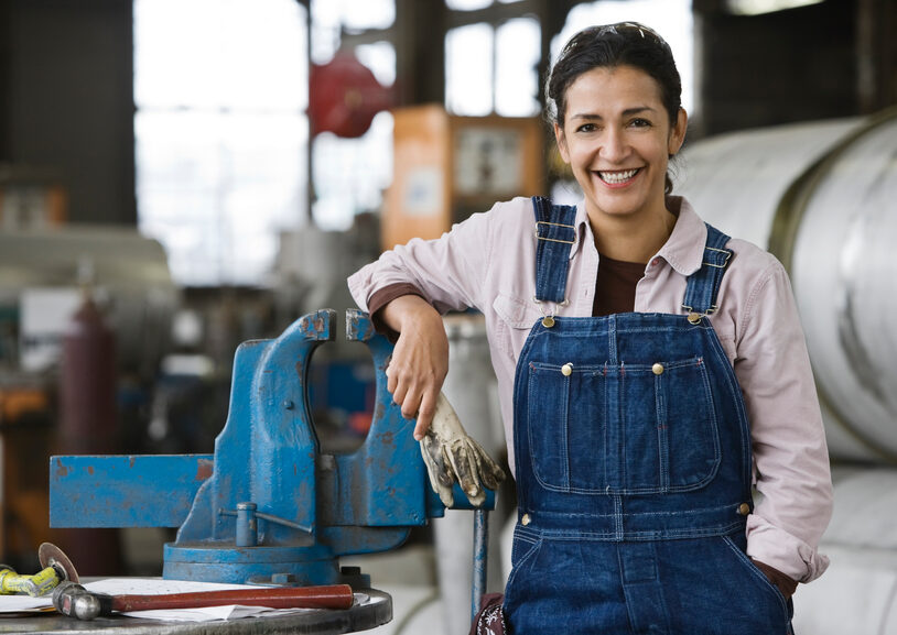 female factory worker smiling in overalls as she leans on equipment