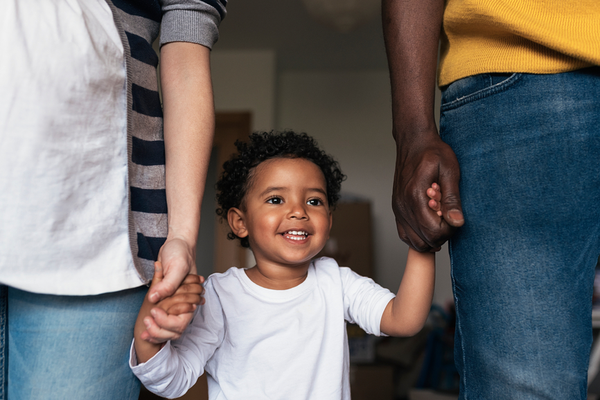 biracial family standing while little boy holds his parents hands