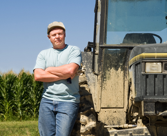 farmer leaning against tractor in a corn field with